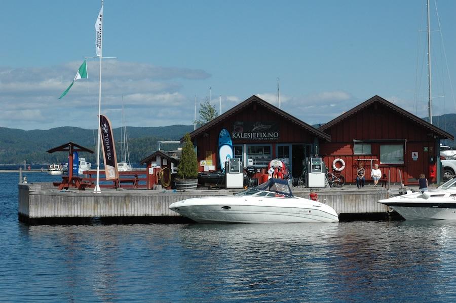 Hvit båt fortøyd til brygge