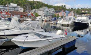 Hvite båter på en brygge med båtkalesjer