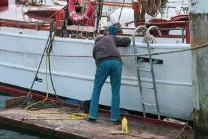 Mann som vasker en hvit båt