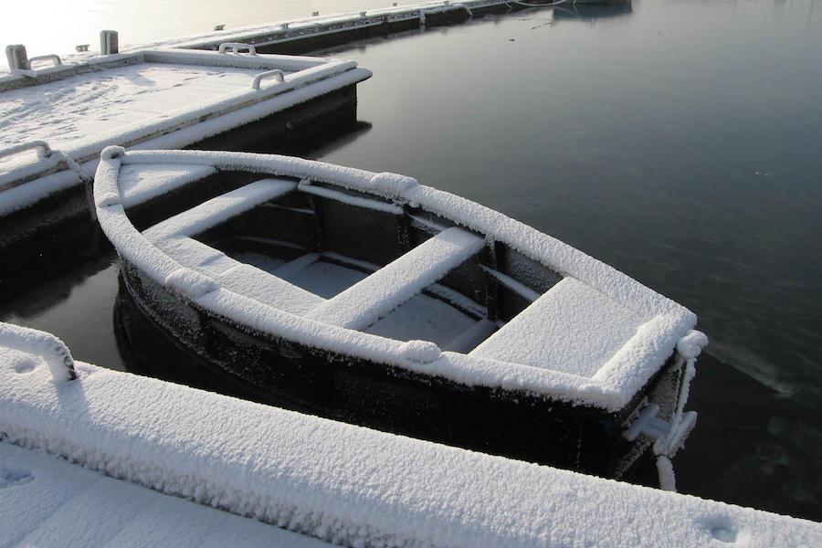 Båt dekket i snø som ligger ved en brygge