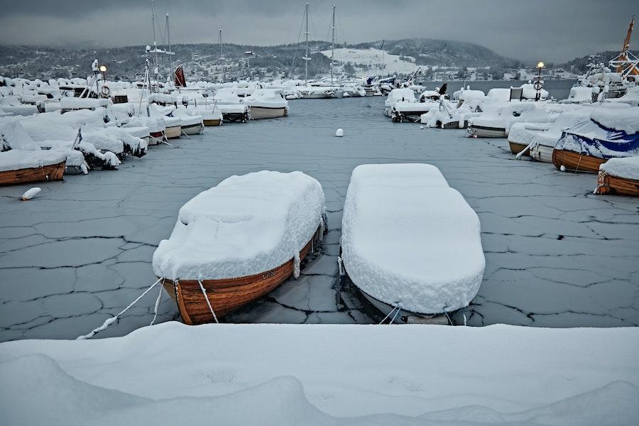 Båter med snø på seg på islagt vann